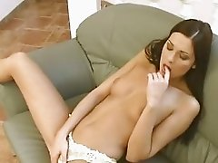 Sexy brunette Evelyn Lory plays her pussy on the sofa