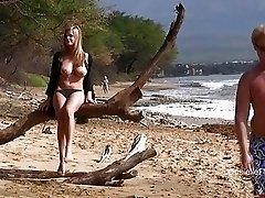 Hot blonde in black bikini reveals her huge bosom on beach
